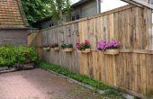 Een Pallet hek met bloembakken en bee hotels